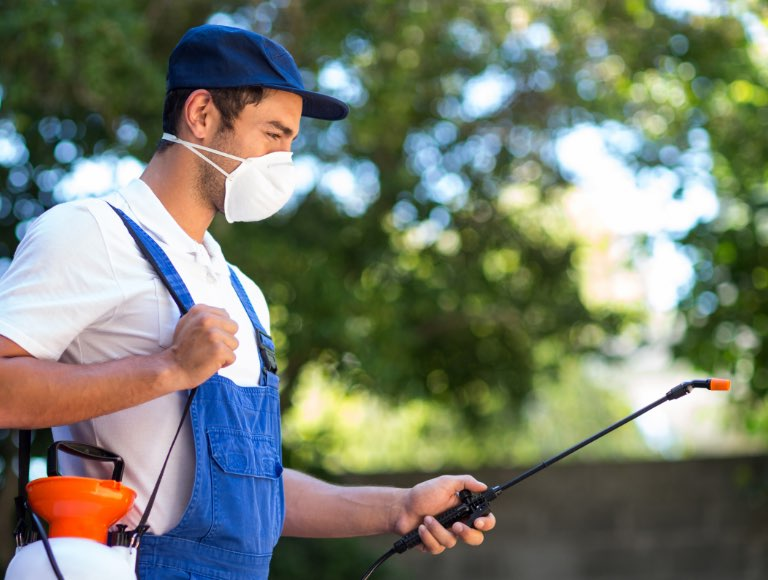 Pest control technician wearing overalls, a ball cap and a mask holding a chemical sprayer
