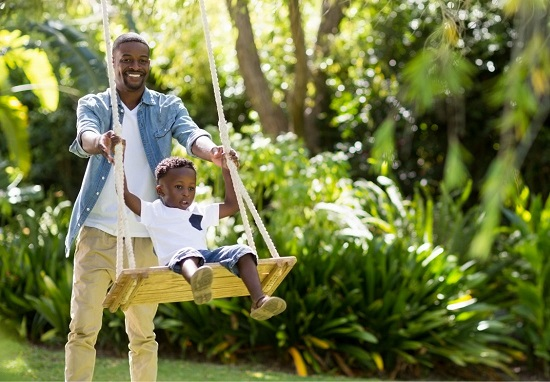 Father pushing his son in a swing